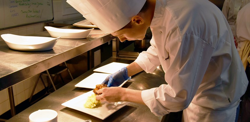 Student plating up a meal in the kitchen
