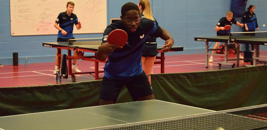 Students playing table tennis in the sports hall